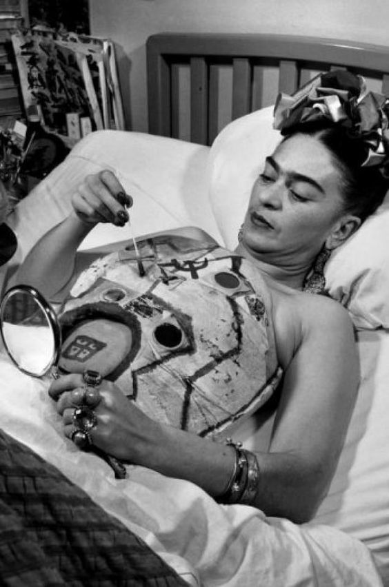 17 - 1951. Frida Kahlo in her hospital bed, painting on her body cast with the help of a mirror. Photo by Juan Guzman.